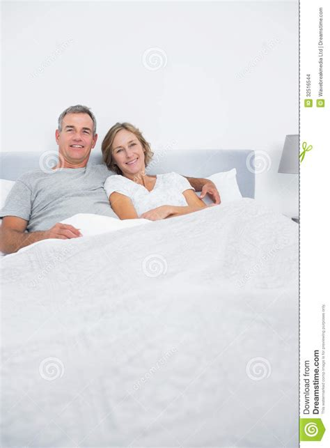 how to cuddle in bed content couple cuddling in bed looking at camera stock