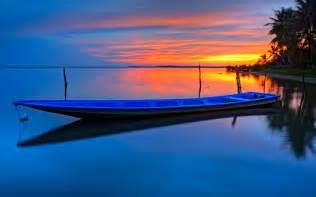 tropical sunset boat palms trees orange sky reflection