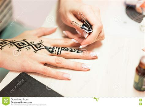 process of applying henna tattoo mehendi on the artist applying henna on mehndi is