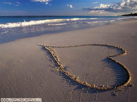 Immagine romantica: spiaggia con cuore su sabbia