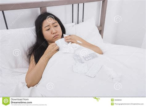 cold bed woman suffering from cold having coffee in bed stock