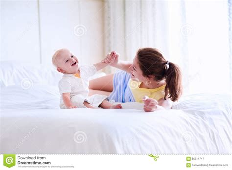 mom son bed mother and baby relaxing in white bedroom stock image