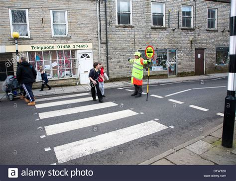 how to get more people on cross road lollipop man stopping traffic to allow people to cross the