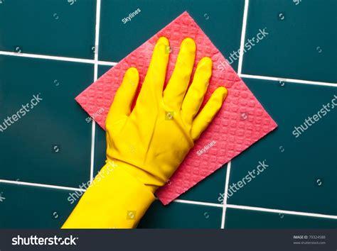 bathroom cleaning sponge hand with yellow sponge cleaning the bathroom tiles stock