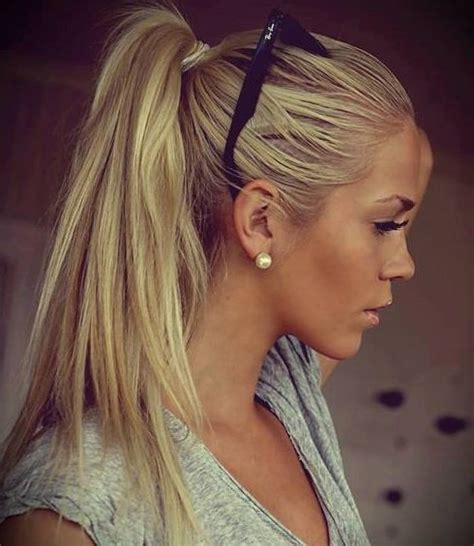 Straight blonde ponytail with golden tan skin large pearl earrings and gray v neck tshirt hot