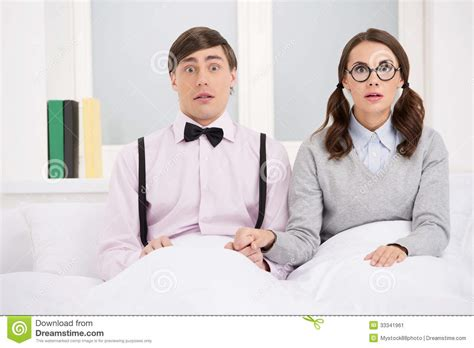 nerdy bedding nerd couple surprised nerd couple sitting on the bed and lookin stock image image