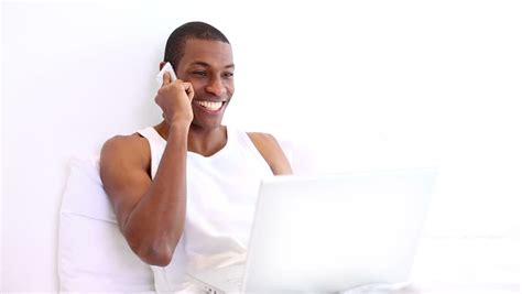 how to make a man happy in bed happy man lying on bed phoning and using laptop at home in