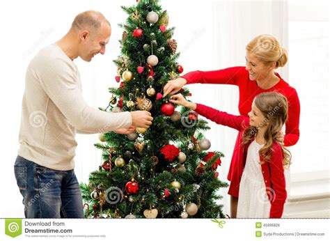 smiling family decorating christmas tree at home stock