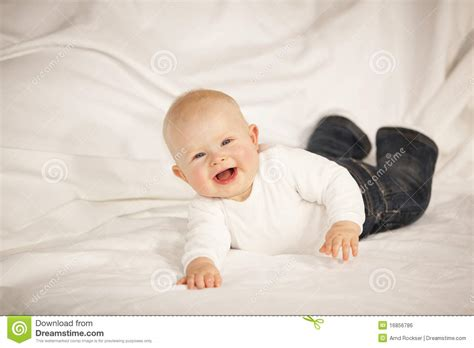 baby on couch laughing baby girl lying on a couch royalty free stock