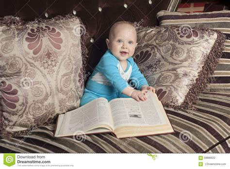 baby on couch baby with book stock photo image 58886622