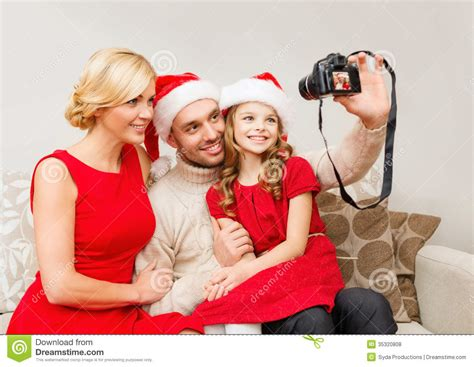 how to take a picture of a christmas tree smiling family in santa helper hats taking picture royalty free stock photos image 35320808