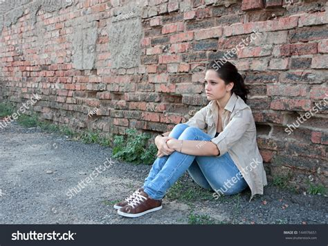 Against A Brick Wall sad sitting against brick stock photo 144976651