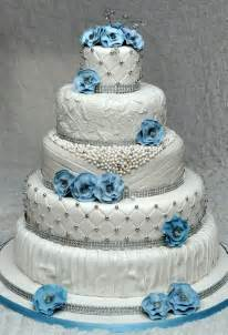 5 tier wedding cake with edible pearls and lace decorated with fondant flowers with lots of