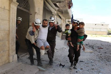 Syrian civil defense volunteers evacuate a man and children from a