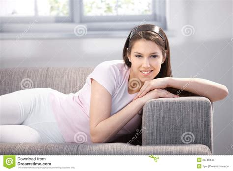 laid on the couch pretty girl laying on sofa smiling stock photos image