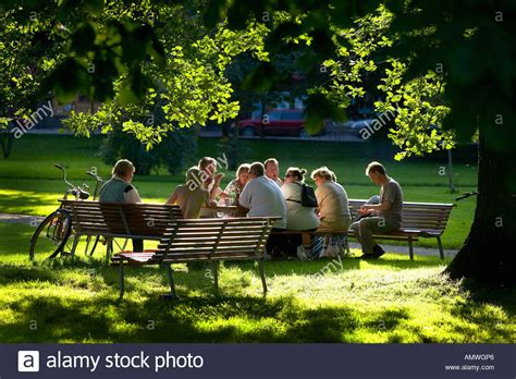 park bench people park bench group group of people sitting on benches in a park on a