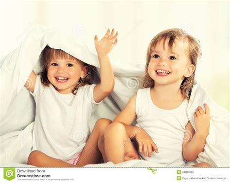 a letto con la sorella le bambine felici gemella la sorella a letto nell ambito