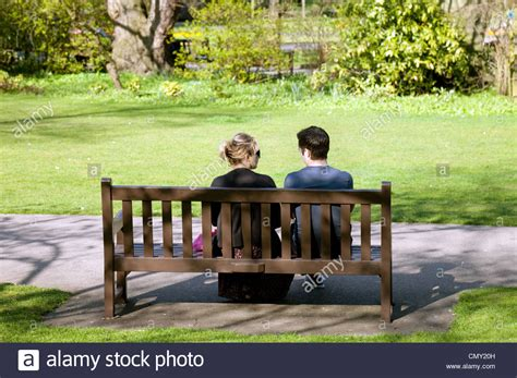 people sitting on a park bench a young couple sitting on a park bench rear view abbey