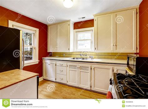 raw kitchen cabinets white kitchen cabinets with bright red wall stock photo