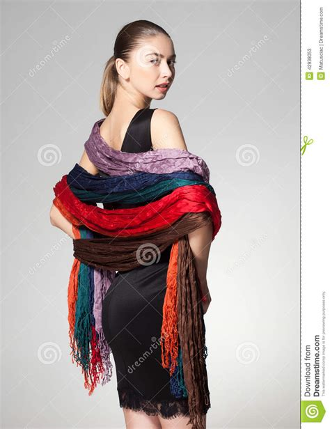 wearing a collection of scarves on grey background