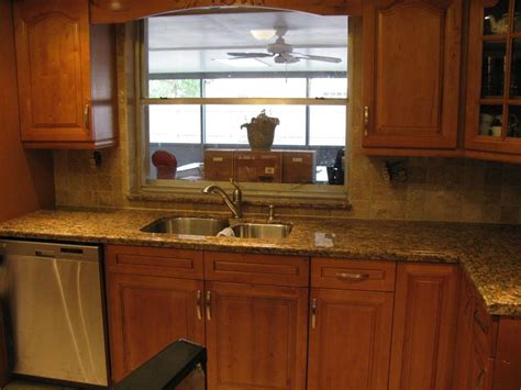 a beautifully installed kitchen with tumbled stone backsplash