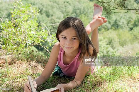 free nudiste family gallery nudiste women ado girls lying on front with book stock photo getty images