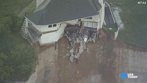 houses falling off cliffs couple looks on as house falls off cliff