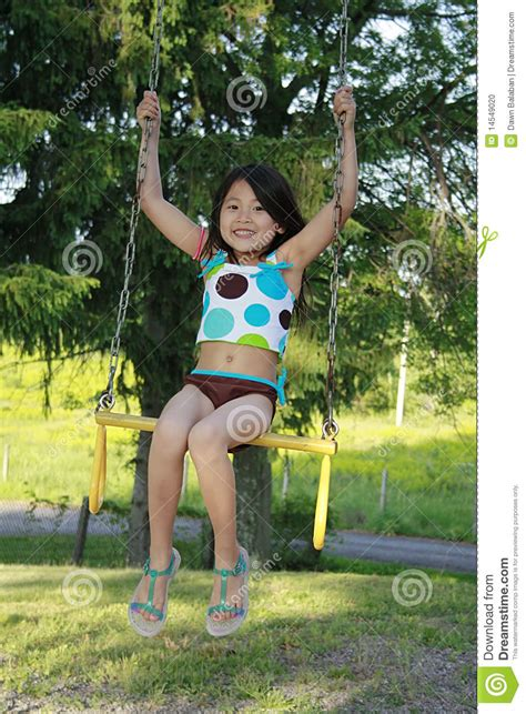 swing asia little asian girl swinging on a swing stock photo image
