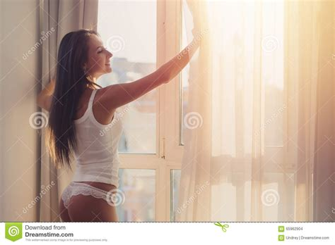 woman opening curtains lovely woman is awoke and standing before window girl