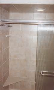 stall shower with tiled walls featuring decorative trim