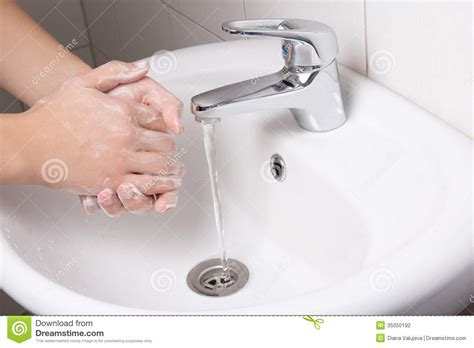 wash the bathroom man washing his hands in bathroom sink stock photo image
