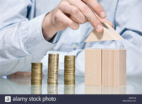 buying a house with another person person building house with building bricks beside stack of coins stock photo royalty