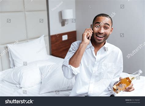 how are nigerian men in bed african man shirt talking phone on stock photo 551784367