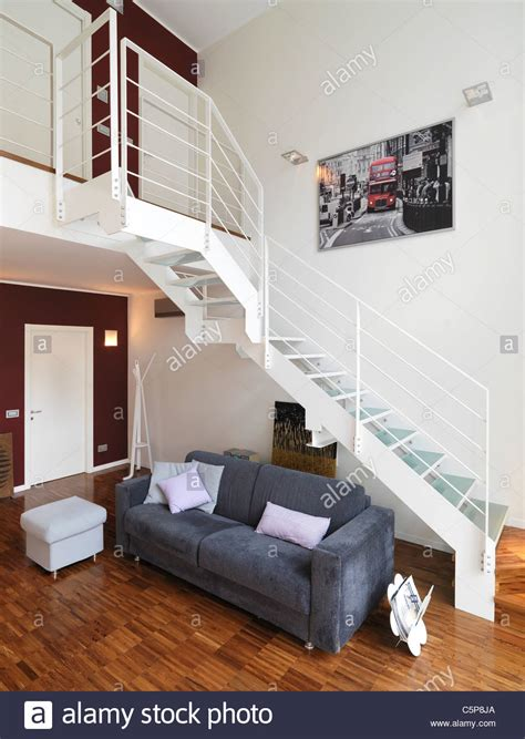 Modern Living Room With Gray Sofa Under A Metal Staircase