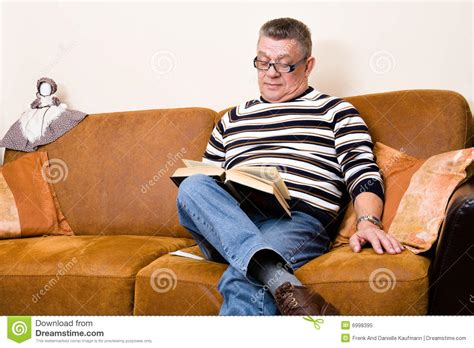 reading couch senior reading his book on the couch royalty free stock