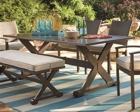 outdoor dining table with bench seating out is in outdoor living space essentials ashley