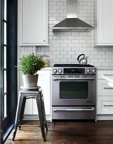 kitchen with white tile backsplash and walnut floors