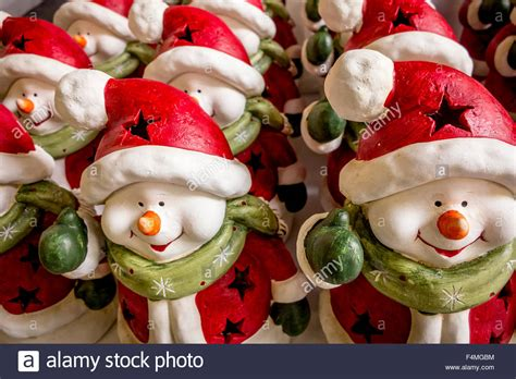 snowmen ornaments in father christmas outfits lined up for