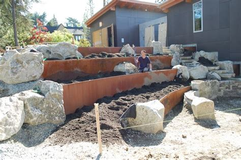 incorporate boulders and metal retaining wall into garden tub surroundings for an urban privacy