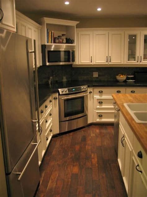 kitchen layout with stove in the corner walnut hardwood flooring in white kitchen with black