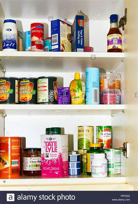 A well stocked food kitchen cupboard with packets and tins