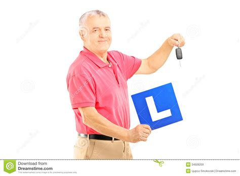 Holding L smiling senior holding a l plate and car key royalty