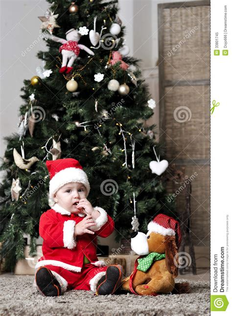 baby in santa costume sit near decorating christmas tree