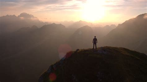 man standing on mountain top aerial flyover silhouette of a man standing on top of