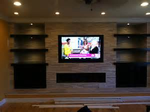 Stacked stone fireplace tiled around tv and book shelves tile
