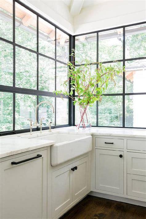 Farmhouse sink under steel windows transitional kitchen