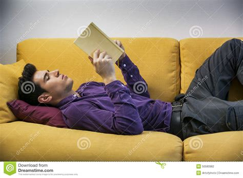 laying couch handsome black haired young man reading book at stock