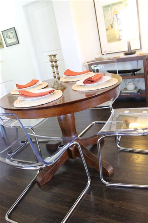 acrylic chairs paired  traditional wood pedestal table