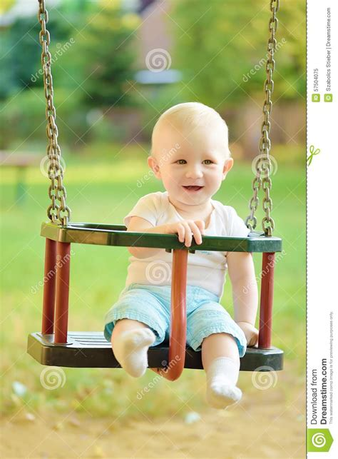 swing for baby boy happy baby boy having fun on a swing ride at a playground