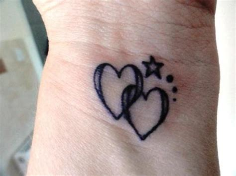 tiny heart tattoo on wrist two black small linked hearts with
